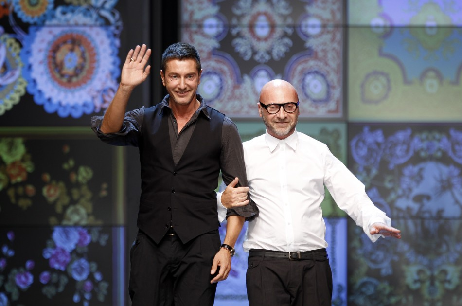 Italian designers Dolce and Gabbana acknowledge the applause at the end of DG SpringSummer 2012 womens collection during Milan Fashion Week