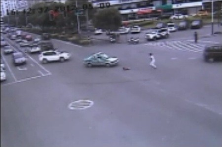The traffic camera clearly shows a child slipping out of the people carrier in Wenzhou city in China's Zhejiang province.