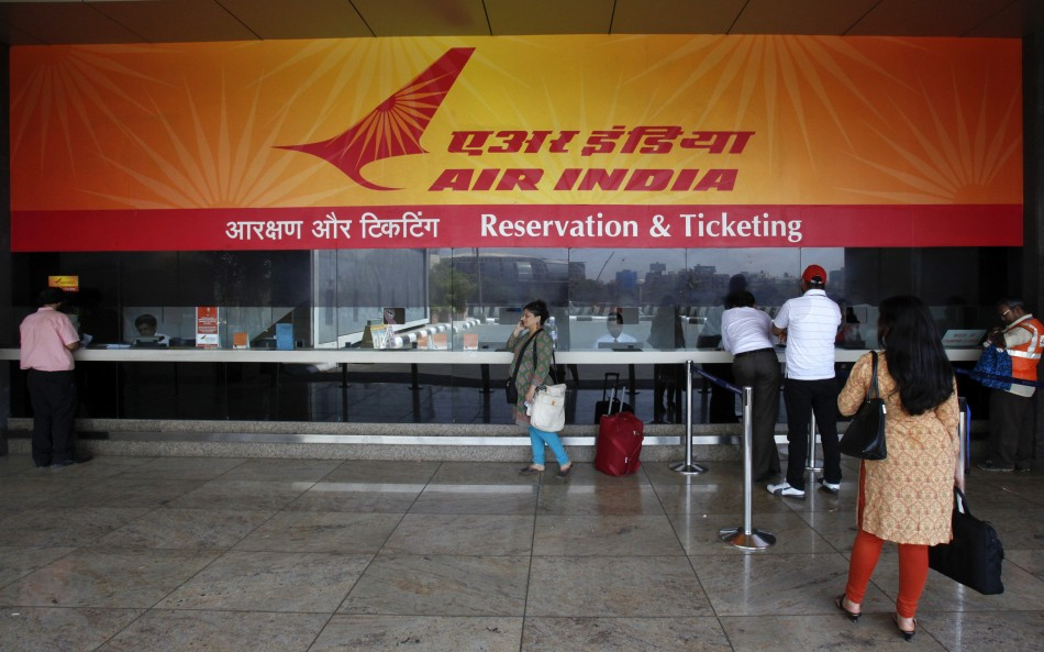 Customers stand at an Air India reservation office at domestic airport in Mumbai