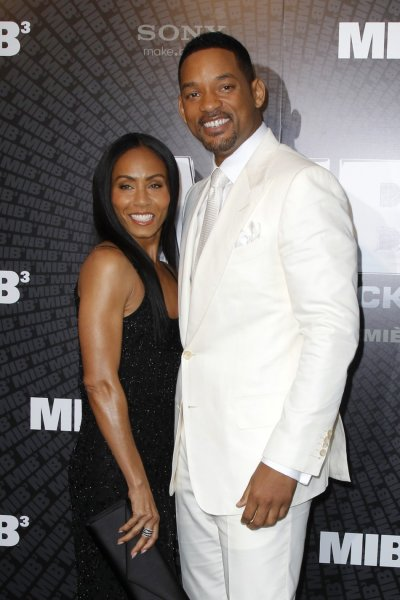 Cast member Will Smith and his wife Jada Pinkett Smith pose as they arrive for a photocall to promote his upcoming film quotMen in Black IIIquot in Paris