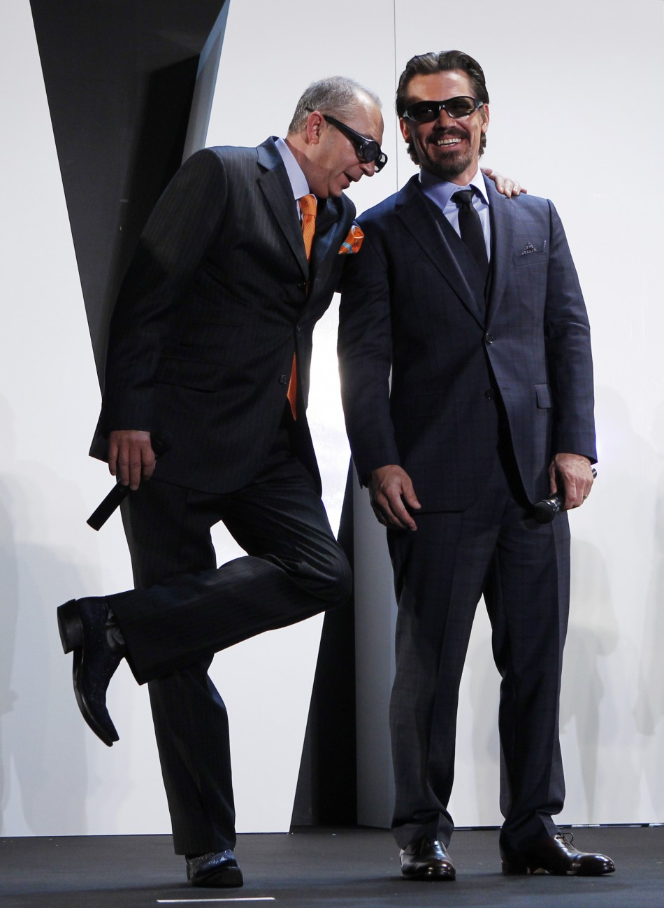 Director Barry Sonnenfeld leans on his cast member Josh Brolin to stretch his leg on a stage at a red carpet event in Japan