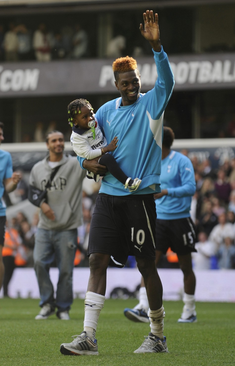 Adebayor, who was on a season-long loan at Tottenham from Manchester City, holds his daughter as he waves to fans after the English Premier League match against Fulham at White Hart Lane