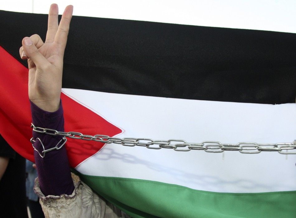 A  woman flashes the peace sign in front of the Palestinian flag