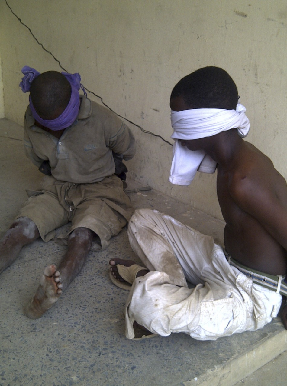 Men suspected to be members of Islamic sect Boko Haram sit blindfolded in the Nigerian city of kano