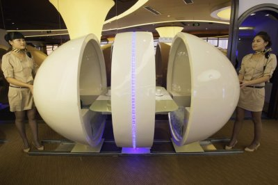 Waitresses reveal an egg-shaped dining-table at an A380 theme restaurant during a media event before its official opening in Chongqing municipality