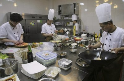 Chefs prepare food inside the kitchen of an A380 theme restaurant, in Chongqing municipality