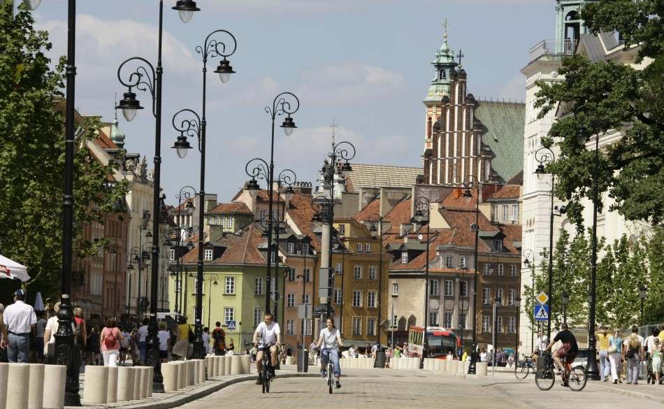 People ride bicycles through the newly renovated Krakowskie Przedmiescie near the old city of Warsaw