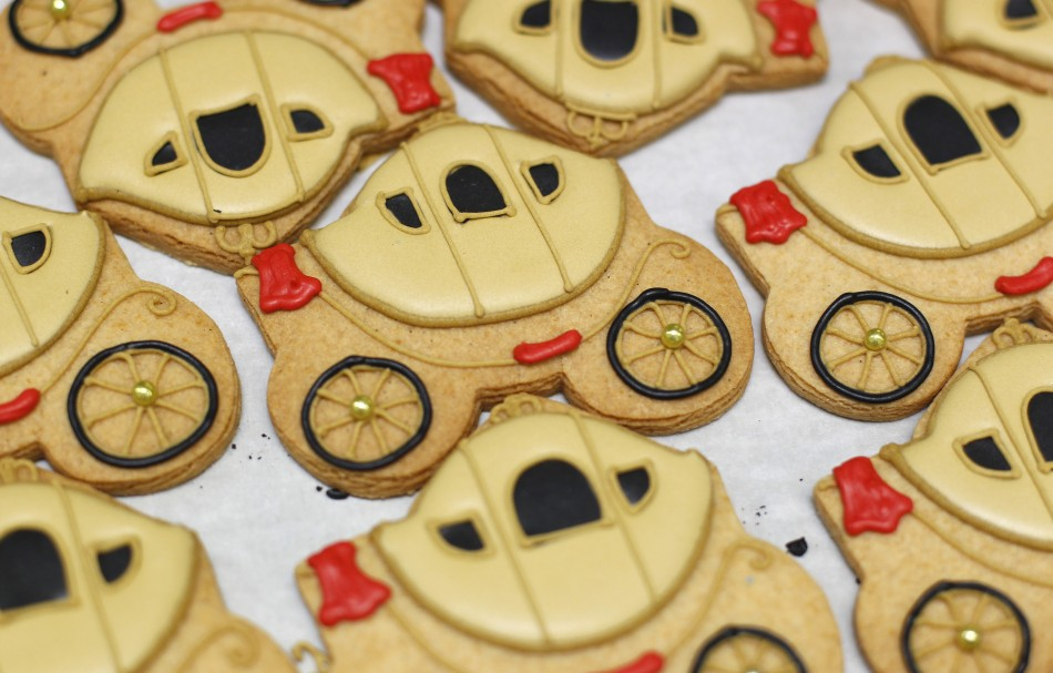 Biscuits depicting a royal carriage sit on trays at Biscuiteers in London