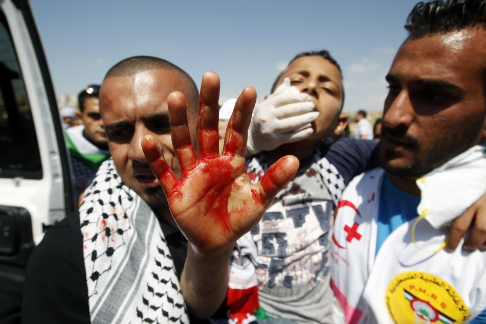 A medic carries an injured Palestinian boy during clashes outside Ofer prison near Ramallah