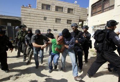 A Palestinian suspected of throwing stones in detained by undercover Israeli police officers in Issawiya