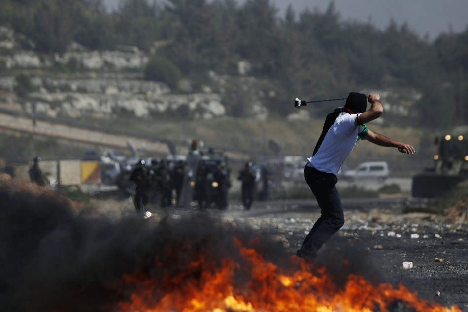 A Palestinian protester uses a sling to hurl stones at Israeli troops during clashes on Nakba day