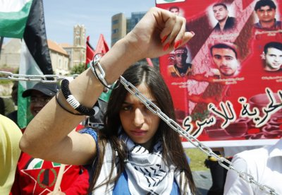 A woman of the youth Palestinian Democratic Union chains herself during a protest to mark the 64th anniversary of Nakba in Beirut