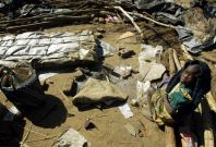 A young Zimbabwe girl sits amidst the rubble of her family's destroyed home in Porta Farm squatter camp