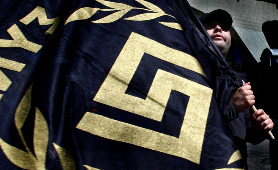 Member of Greece's extreme-right Golden Dawn party holds flag bearing party logo during election campaign rally in Athens