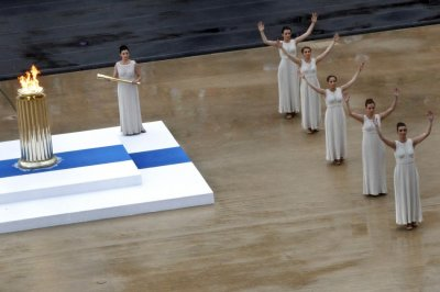 Actresses, in the role of ancient priestesses, dance during an Olympic Flame handover ceremony in Athens