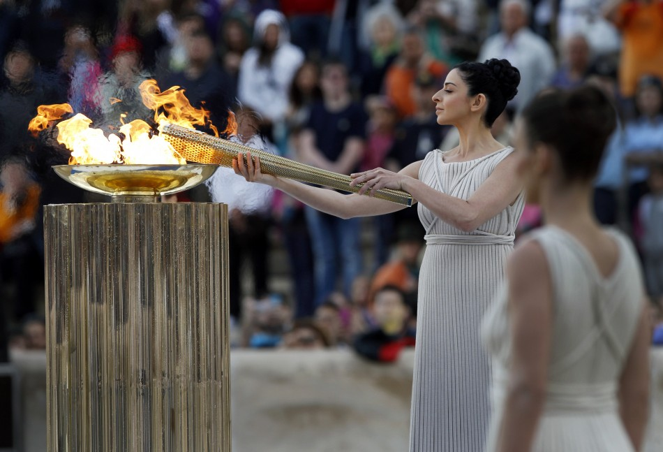 Ino Menegaki, a Greek actress, in the role of an ancient high-priestess, lights a torch from a cauldron with the Olympic Flame