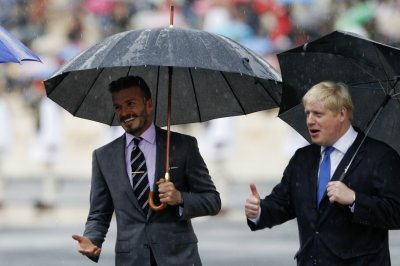 David Beckham and London039s Mayor Boris Johnson enter the Panathenaic stadium before an Olympic Flame handover ceremony in Athens
