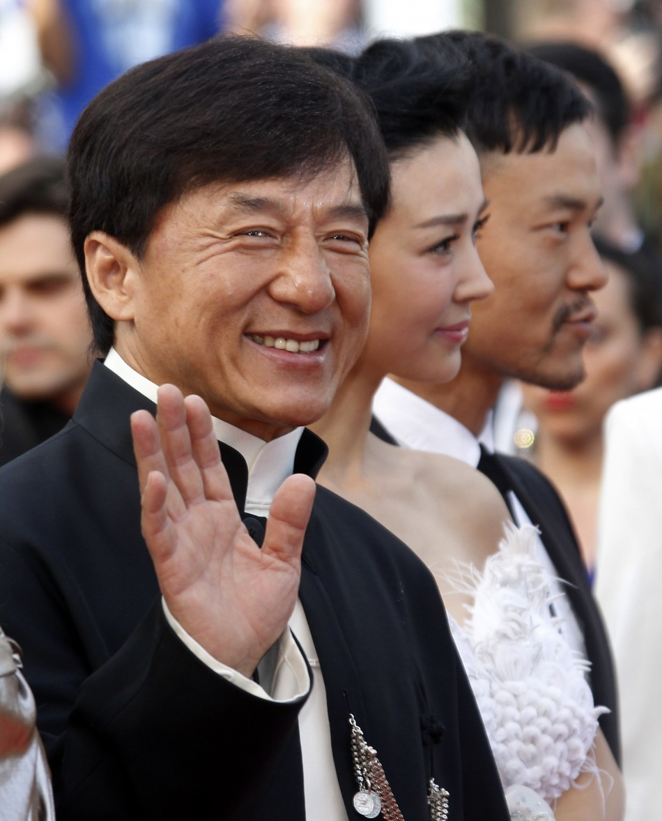Actor Chan waves as he arrives on the red carpet with unidentified guests for the screening of the film De rouille et dos at the 65th Cannes Film Festival