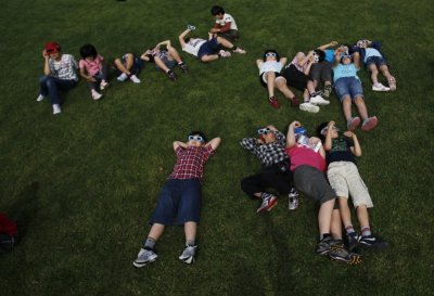 School children using solar viewers lie down on a lawn as they observe an annular eclipse at Hirai Daini Elementary School in Tokyo
