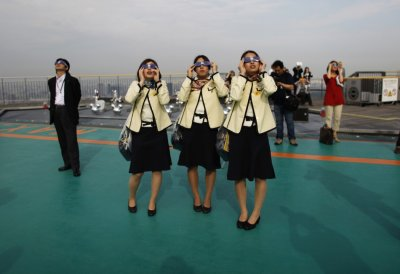 Bus tour guides look at an annular eclipse at a rooftop of the Roppongi Hills complex in Tokyo