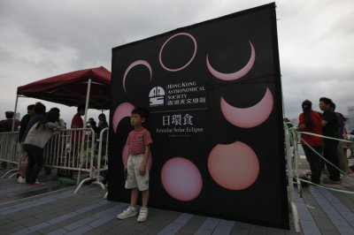 A child poses for pictures in front of a board, which shows the different phases of an annular solar eclipse, in Hong Kong