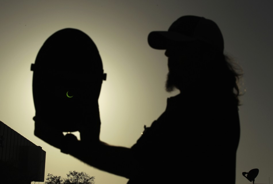 Dennis Vitt, 38, looks at an annular eclipse through a welding mask in Los Angeles