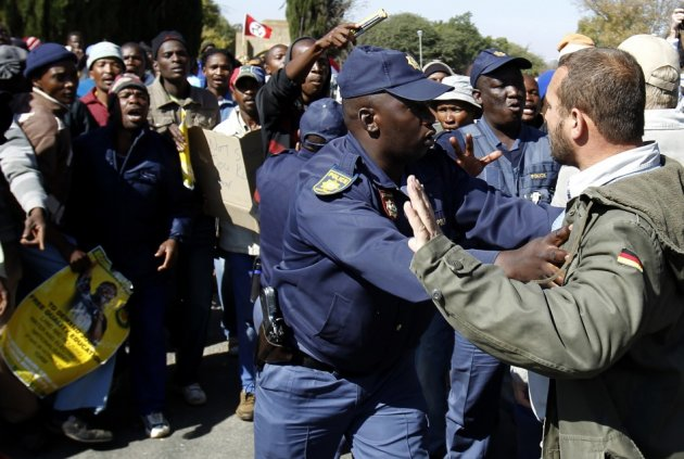 A police officer stops a member of the Afrikaner Resistance Movement (AWB) from approaching supporters of Mahlangu and Ndlovu (Reuters)
