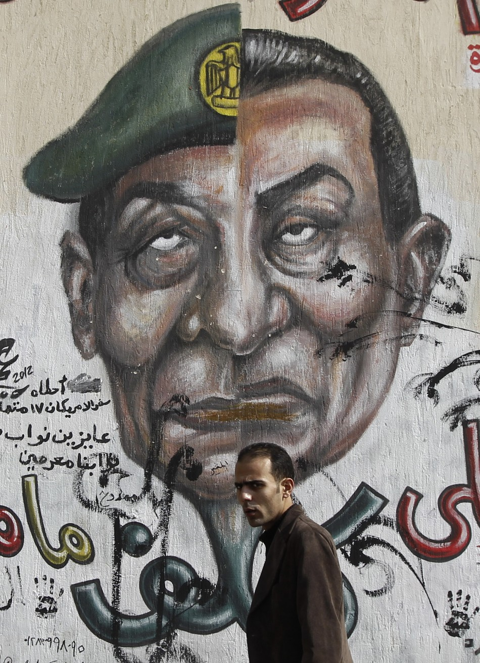 Egyptian man walks past graffiti depicting the faces of former President Mubarak and Field Marshal Tantawi in Cairo