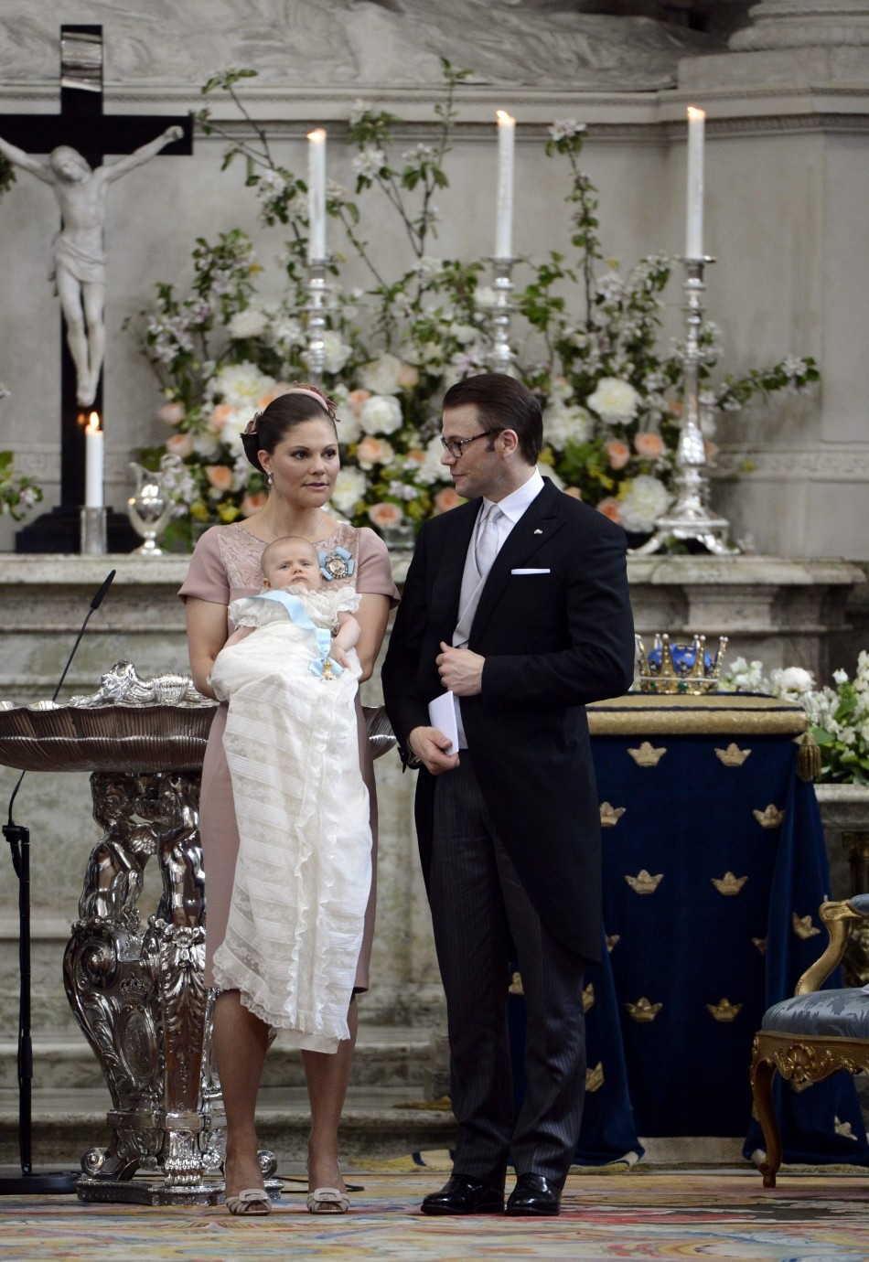 Swedens Crown Princess Victoria holds Princess Estelle as she stands with Prince Daniel after the christening ceremony, held at the Royal Chapel in Stockholm