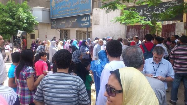 Egyptians queuing at a polling sEgyptians are heading to the polls for their first free presidential elections, 15 months after mass protests ousted former leader Hosni Mubarak