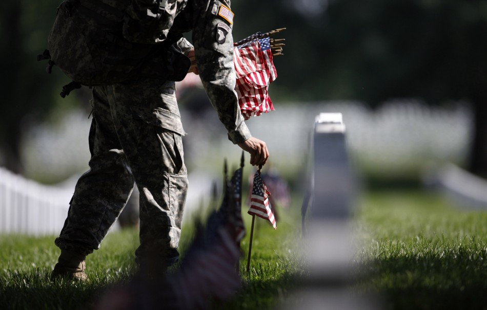 A member of the U.S. Army Old Guard places a flag at one of the over 220,000 graves of fallen U.S. military service members buried at Arlington National Cemetery, May 24, 2012.