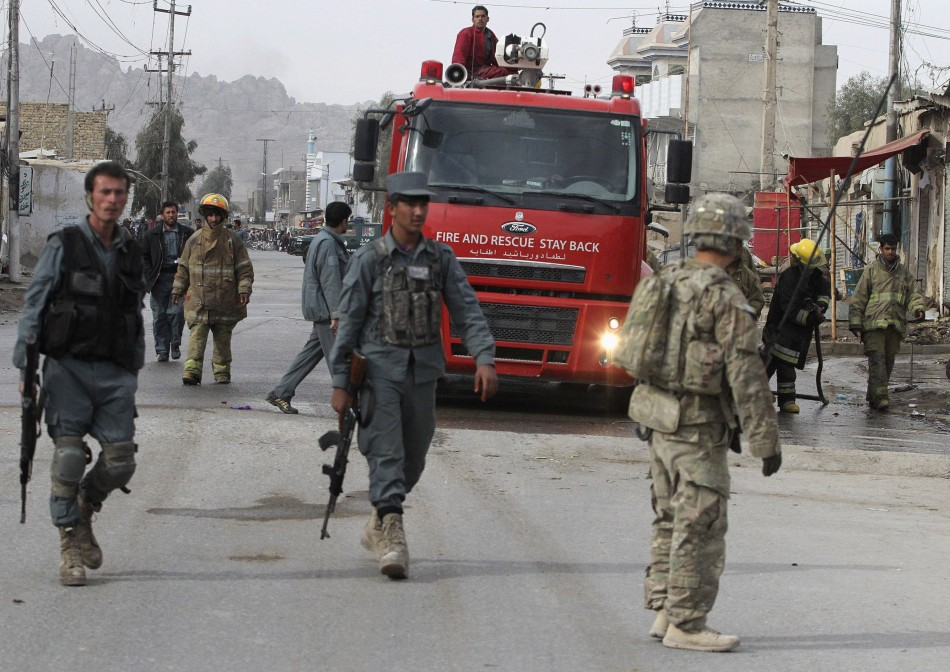 Afghan police officers and foreign soldiers arrive at the site of a suicide attack in Kandahar province in Januray 2012.
