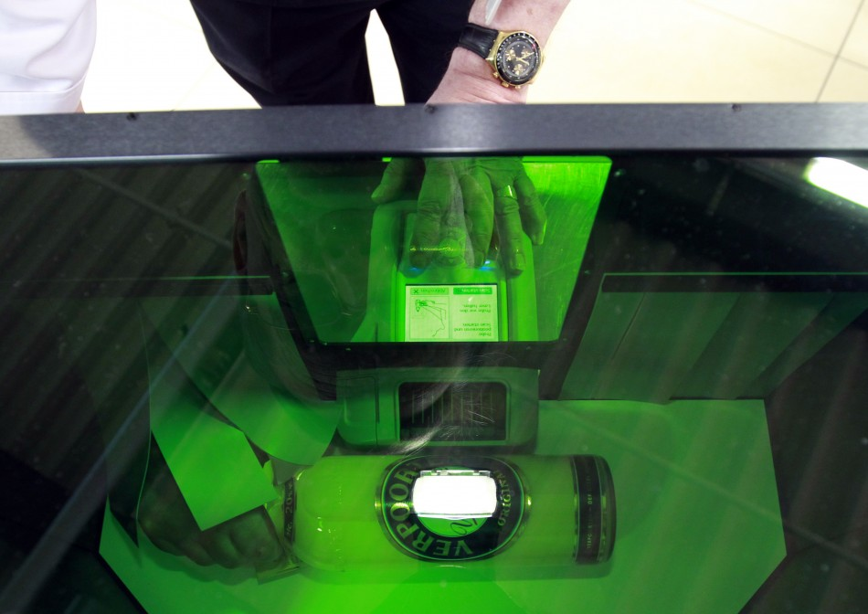 Airport staff demonstrate scanner used to identify dangerous liquids in luggage