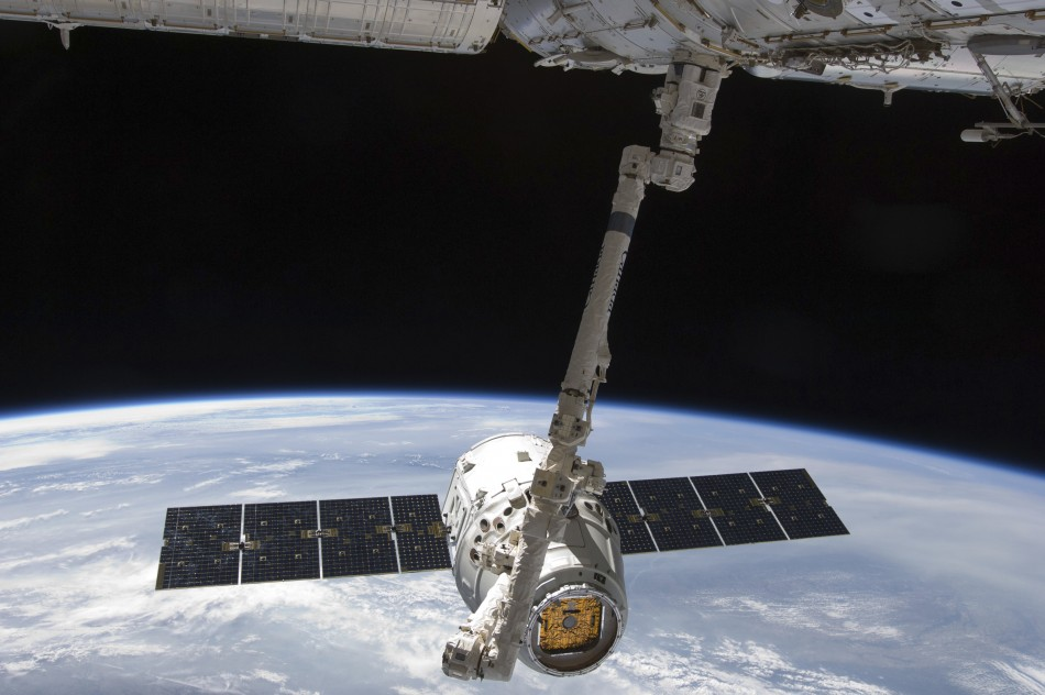 The SpaceX Dragon commercial cargo craft is seen as it is grappled by the International Space Station's Canadarm2 (Reuters/Nasa)