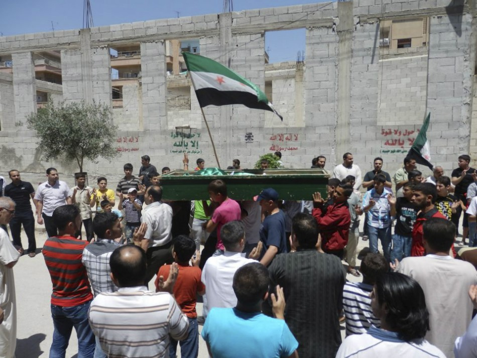 Mourners clap for Yaser Raqieh, who was killed near Hama by forces loyal to regime of Syrian President Bashar al-Assad