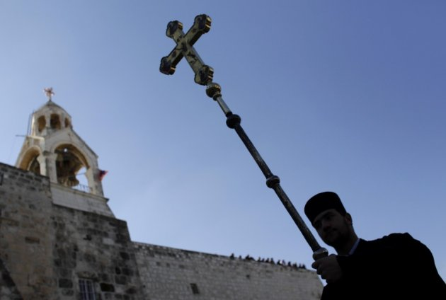 Greek Orthodox priest carries cross beside Church of the Nativity in Bethlehem