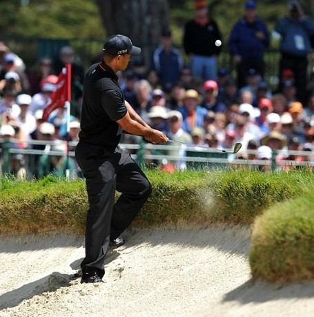 Tiger Woods pops a nearly impossible shot off the lip of a bunker on 6.