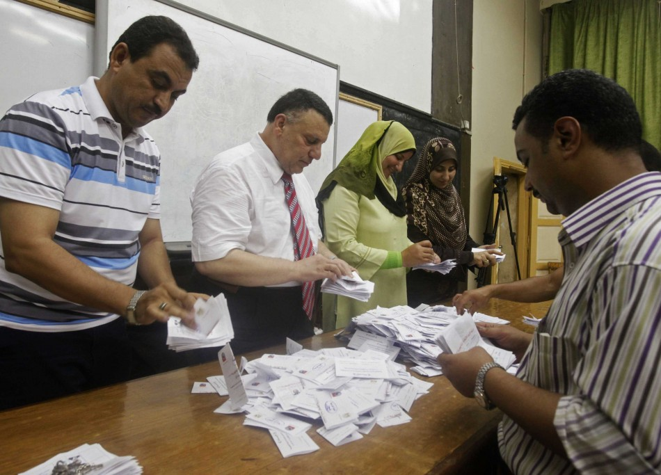 Electoral workers count ballots at polling station in Cairo after polls close in presidential runoff