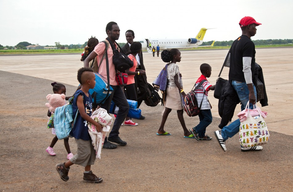 South Sudanese nationals who arrived from Israel walk from their plane at the airport in Juba, Reuters
