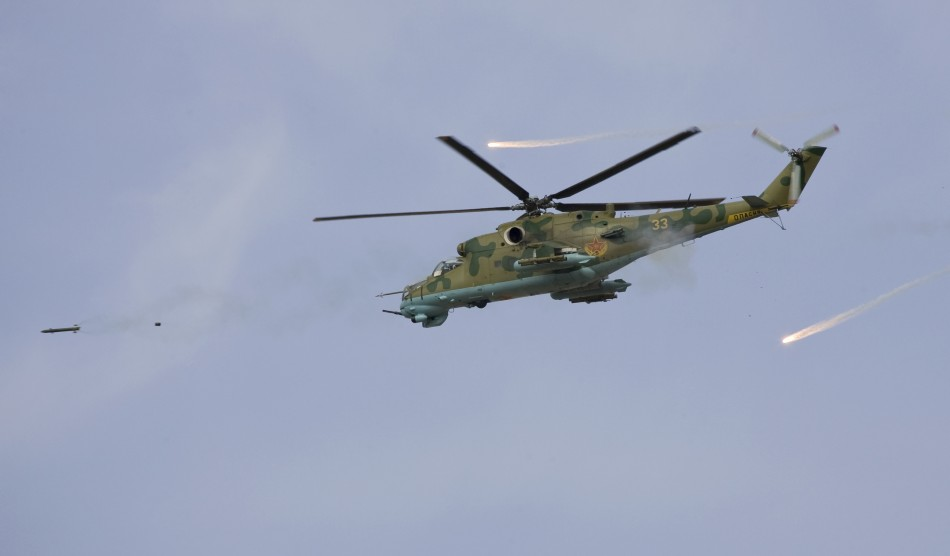 A Russian-made attack helicopter fires a rocket and releases flares