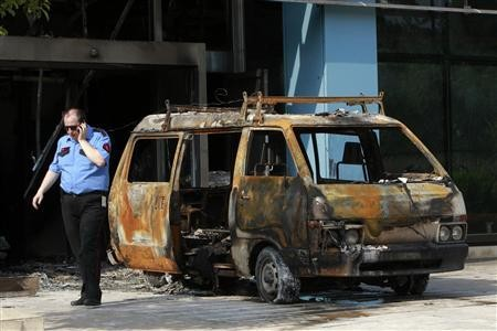 Security guard confers with colleagues by van gutted in attack on Microsoft office in Athens