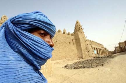 A Tuareg nomad stands near a 13th century mosque in Timbuktu in this file photo , Reuters
