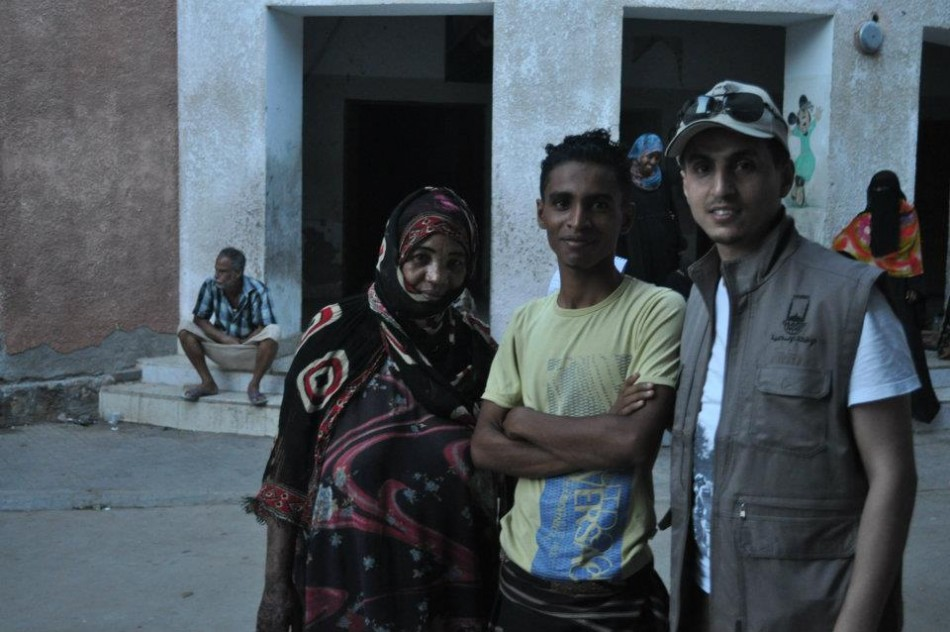 Habib (wearing cap)  is with Majed, 15, and his mother in Aden City, south Yemen. Majed's family is one of more than 28 families who live in this school building as refugees.