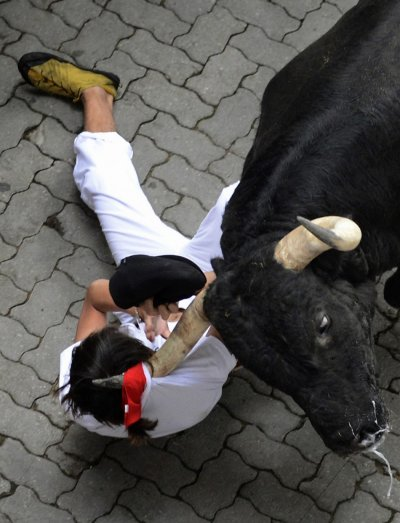 A runner is dragged by his scarf by a Dolores Aguirre fighting bull at the entrance to the bullring during the first running of the bulls of the San Fermin festival in Pamplona