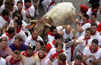 Runners dodge a bull during the San Fermin festival in Pamplona