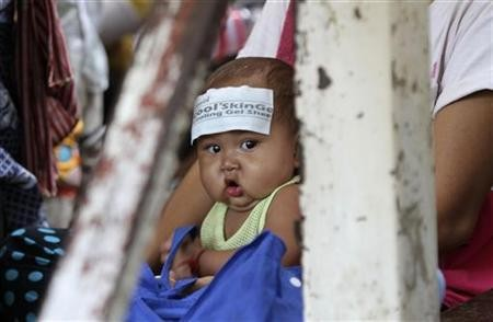 People wait with their children for free medical treatment at Kantha Bopha Hospital in Phnom Penh July 4, 2012 (Reuters)