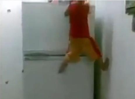 Asian Baby climbs fridge