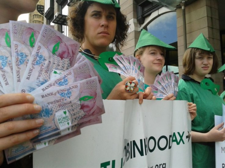 """Top: """"Robin Hood""""-customed demonstrators, demanding a tax on financial institutions, give fake banknotes and coins to consumers at a Barclays bank in London."""