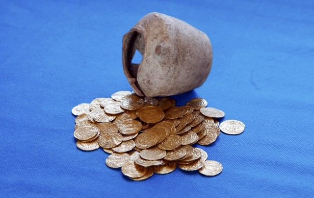 Gold coins and the jar within which they were unearthed during excavations at a Crusader fortress, are displayed near Herzliya. (Photo: REUTERS)