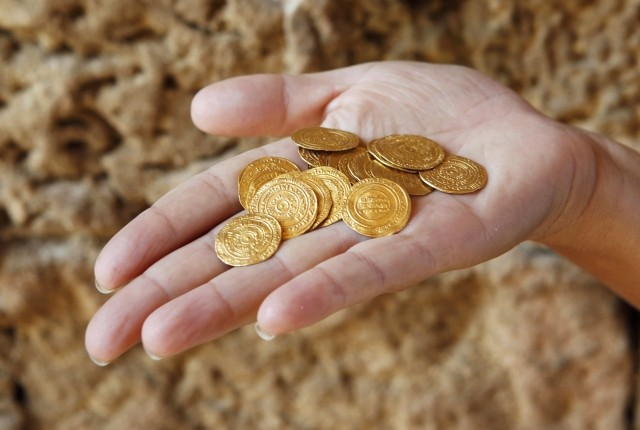 Israel Nature and Parks Authority employee shows gold coins, which were unearthed during excavations at a Crusader fortress, near Herzliya. (Photo: REUTERS)